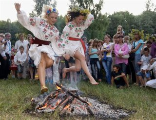 Ukrainian young women dressed in traditional clothing jump over a fire at a traditional Midsummer Night celebration near the capital Kiev late Monday July 6, 2009. The age-old pagan festival is still celebrated in Ukraine and many people believe that jumping over the fire will cleanse them of evil spirits. (AP Photo/Efrem Lukatsky)