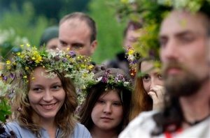 Russian neo-pagans look on while participating in festivities to celebrate the summer solstice in Maloyaroslavets, some 200 kilometers (124 miles) south-west from Moscow, Russia, early Saturday, June 20, 2009. The festivities of Ivan Kupala, or John the Baptist, are similar to Mardi Gras and reflect pre-Christian Slavic traditions and practices. After the 1991 Soviet collapse, Russia has seen a revival of the Russian Orthodox church along with a surge of peripheral movements and creeds.(AP Photo/Sergey Ponomarev)