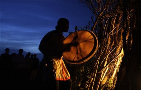 The supreme priest of Russian neo-pagans beats his drum while his followers dance around the bonfire celebrating the summer solstice in Maloyaroslavets, some 200 kilometres south-west from Moscow, Russia, early Sunday, June 21, 2009. The festivities of Ivan Kupala _ or John the Baptist _ is similar to Mardi Gras and reflects pre-Christian Slavic traditions and practices. After the 1991 Soviet collapse Russia has seen a revival of Russian Orthodox church along with a surge of peripheral movements and creeds (AP Photo/Sergey Ponomarev)